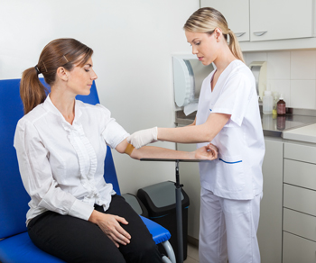 Healthcare provider drawing blood from woman's arm.